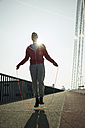 Young man skipping rope on bridge - UUF000402