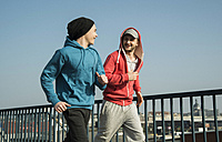 Young man and teenager running on bridge - UUF000406