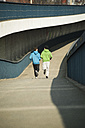 Young man and teenager running on bridge - UUF000407