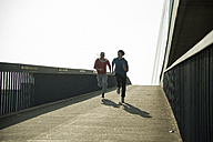 Young man and teenager running on bridge - UUF000429