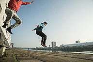 Young man and teenager jumping mid air - UUF000463