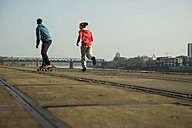 Young man and teenager jogging and skateboarding - UUF000446