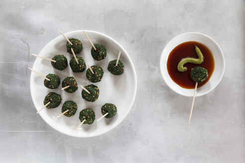 Plate of skewered spinach sesame balls and dipping bowl of sauce, elevated view - EVGF000554