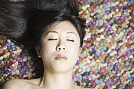 Portrait of Asian woman with closed eyes in front of colourful ground - FLF000500