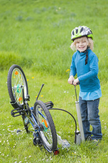 Little boy inflating bicycle tire on a meadow - MJF001082