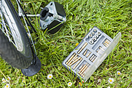 Tool kit for repairing bicycle lying in grass - MJF001092