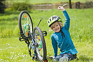 Portrait of smiling little boy repairing bicycle on meadow - MJF001090