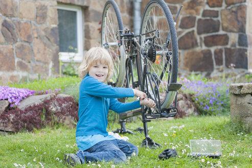 Portrait of smiling little boy repairing bicycle in garden - MJF001086