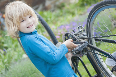 Portrait of smiling little boy repairing bicycle - MJF001087