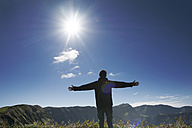 Portugal, Azores,Sao Miguel, Man standing with arms outstretched at Caldeira das Sete Cidades - ONF000445