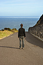 Portugal, Azores, San Miguel, man standing on street looking to the sea - ONF000472