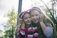 Two sisters with pink headphones hearing music together - SARF000554