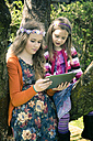 Two sisters with tablet computer together in garden - SARF000570