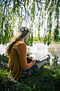 Female teenager with book sitting under weeping willow - SARF000572