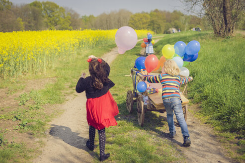 Three children on the move with wooden trolley and balloons - MJF001094