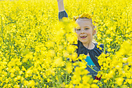 Little girl sitting in rape field - MJF001157