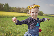 Little girl with outstretched arms standing on a meadow - MJF001126
