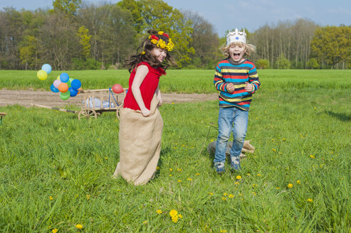 Two children sack racing on meadow - MJF001130