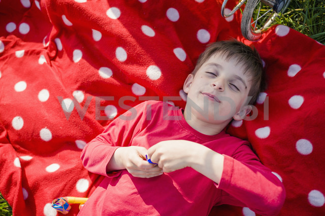 Smiling boy with closed eyes lying on red-white Polka Dot blanket - MJF001146