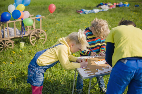 Children painting paper crowns  for birthday party - MJF001149