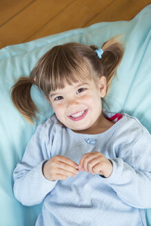 Portrait of smiling little girl lying on bean bag, elevated view - LVF001159