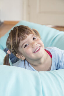 Portrait of smiling little girl lying on bean bag - LVF001166