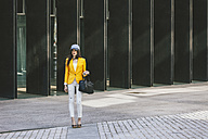 Spain,Catalunya, Barcelona, young modern woman with yellow jacket on the move - EBSF000206