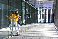 Spain,Catalunya, Barcelona, young modern woman with yellow jacket leaning against glass facade - EBSF000198