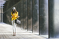 Spain,Catalunya, Barcelona, young modern woman with yellow jacket on the move - EBSF000215