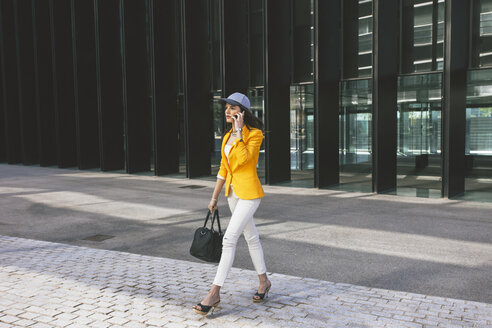 Spain,Catalunya, Barcelona, young modern woman with yellow jacket on the move - EBSF000192