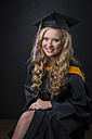 Portrait of young female graduate wearing mortarboard - ABAF001318