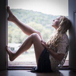 Portrait of young woman sitting on window sill looking above - ABAF001322