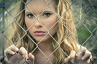 Portrait of young woman behind wire fence - ABAF001326