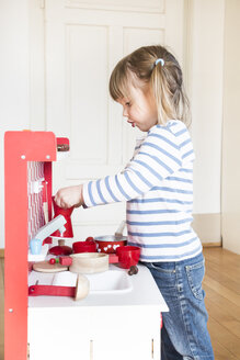Little girl playing with children's kitchen - LVF001175
