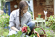 Young woman with red radishes in vegetable garden - SGF000634