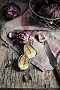 Whole and sliced baby artichokes, kitchen towel and knife on wooden table - SBDF000797