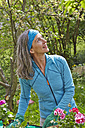 Mature woman in garden looking up - AKF000374