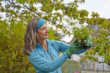 Woman in garden holding flower - AKF000387