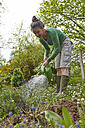 Mature woman watering flowers in garden - AKF000389