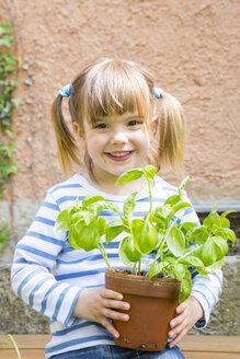 Portrait of smiling little girl holding flowerpot with basil - LVF001187