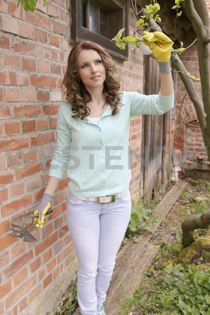 Woman looking at twig of tree - VTF000220 - Val Thoermer/Westend61