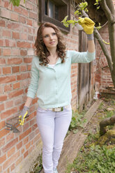 Woman looking at twig of tree - VTF000220