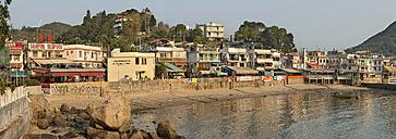 China, Hong Kong, Lamma Island, waterfront with houses and boat in Yung Shue Wan bay - SHF001240