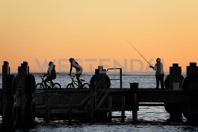 Australia, Western Australia, Lancelin, three people on a pier at sunset - MIZ000478