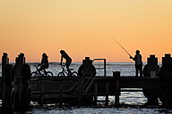 Australia, Western Australia, Lancelin, three people on a pier at sunset - MIZ000478