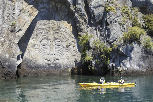 New Zealand, view to Maori cave art with two tourists in kayak in front - STD000083