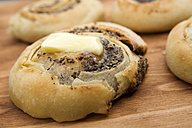 Baked poppy yeast dough roll with piece of melting butter on wooden table - CSTF000331