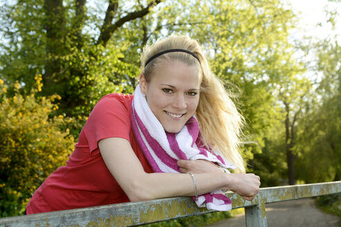 Portrait of smiling young woman leaning on railing - BFRF000408