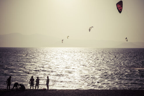 Greece, Cyclades, Naxos, Mikri Vigla, Orkos Beach with kite and windsurfer at sunset - KRP000471