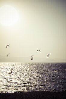 Greece, Cyclades, Naxos, Mikri Vigla, Orkos Beach, Kite- and windsurfer at sunset - KRP000474